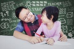 Male teacher teach little girl in class Stock Image