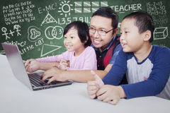 Male teacher teach two students with laptop. Portrait of young teacher teaching two little students with laptop computer in the classroom Stock Image