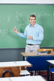 Male Teacher Teaching Mathematics On Board Royalty Free Stock Image