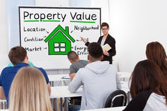 Male Teacher Teaching Property Value To Students. A Male Teacher Explaining The Concept Of  Property Value Concept To Students In Classroom Royalty Free Stock Photos