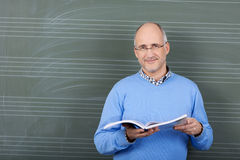 Male teacher with a text book in his hands. Smiling male teacher with a text book in his hands standing in front of the blackboard in the schoolroom with Royalty Free Stock Image