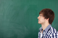 Male Teacher Thinking In Front Of Chalkboard. Portrait of handsome young male teacher thinking in front of chalkboard Royalty Free Stock Photo