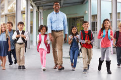 Male teacher walking in corridor with elementary school kids Stock Images