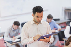 Male teacher working concentrated with his tablet Stock Images