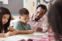 Male teacher working with elementary school boy at his desk royalty free stock photos