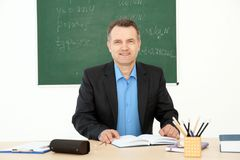 Male teacher working at table. In classroom Royalty Free Stock Image