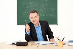 Male teacher working at table. In classroom Royalty Free Stock Photos