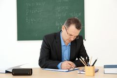 Male teacher working at table. In classroom Stock Photos