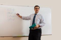 A male teacher writes on a blackboard Stock Image