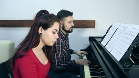 Male teacher with young girl student playing piano in musical school. Music class for adults. People making music together stock video footage