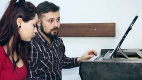 Male teacher with young girl student playing piano in musical school. Music class for adults. People making music together stock video