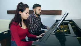 Male teacher with young girl student playing piano in musical school. Music class for adults. People making music together stock footage