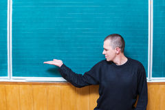 Male teachers in the classroom before board. Man in a sweater is standing in front of a school board reaching out his hand Royalty Free Stock Photography