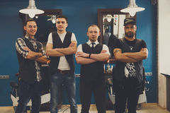 Male team of barbers at modern barbershop. Team of barbers in modern barbershop. Four masculine male hairstylists standing indoors at workplace in hair salon Royalty Free Stock Photos