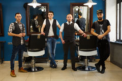 Male team of barbers at modern barbershop. Team of young professional barbers posing to camera inside modern barbershop. Four masculine male hairstylists Stock Photos