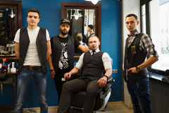 Male team of barbers at modern barbershop. Team of young professional barbers posing to camera inside modern barbershop. Four masculine male hairstylists Stock Photography
