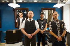 Male team of barbers at modern barbershop. Young professional barbers team posing to camera inside modern barbershop. Four masculine male hairstylists standing Stock Photo