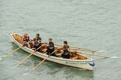 Male team on rowing boat at Clovelly, Devon Stock Image