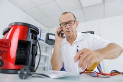 Male tech on phone fixing vaccum cleaner. Male tech on the phone is fixing a vaccum cleaner Royalty Free Stock Photos