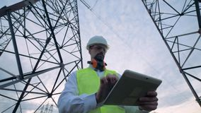 Male technician is browsing a computer while being near electricity towers. HD stock video footage