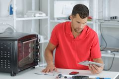 Male technician checking tablet to repair oven in kitchen Stock Photo
