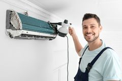 Male technician cleaning air conditioner. Indoors Stock Image