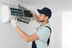 Male technician cleaning air conditioner. Indoors Stock Photo