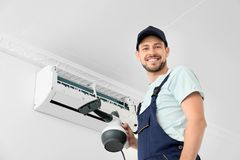 Male technician cleaning air conditioner. Indoors Royalty Free Stock Images