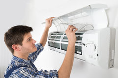 Male Technician Cleaning Air Conditioning System. Young Male Technician Cleaning Air Conditioning System At Home Royalty Free Stock Image