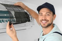 Male technician cleaning air   indoors. Male technician cleaning air conditioner indoors Royalty Free Stock Photo