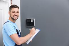 Male technician with clipboard near installed alarm system. Indoors Stock Image