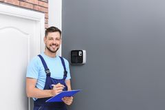 Male technician with clipboard near installed   system. Male technician with clipboard near installed alarm system indoors Stock Photo