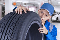 Male technician controls a tire. Young asian technician with a blue workwear checking a black tire in the workshop Stock Photography
