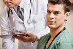 Male Technician With Doctor In Background. Portrait of male technician with doctor holding digital tablet in background Stock Photography