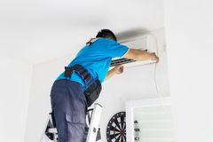 Male technician fixing an air conditioner. Back view of a male technician fixing an air conditioner at home Royalty Free Stock Photography
