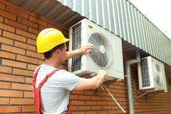 Male technician fixing air conditioner. Outdoors Stock Photos