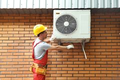 Male technician fixing air conditioner. Outdoors Royalty Free Stock Photo