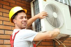 Male technician fixing air conditioner. Outdoors Royalty Free Stock Image