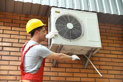 Male technician fixing air conditioner. Outdoors Stock Photo