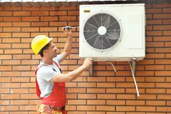 Male technician fixing air conditioner. Outdoors Royalty Free Stock Images