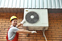 Male technician fixing air conditioner. Outdoors Royalty Free Stock Photography