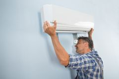 Male technician fixing air conditioner. Portrait Of A Mid-adult Male Technician Fixing Air Conditioner On Wall Stock Photo