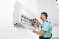 Male technician fixing modern air conditioner. Indoors Royalty Free Stock Photography