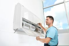 Male technician fixing modern air conditioner. Indoors Royalty Free Stock Image