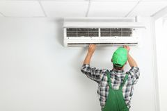 Male technician fixing modern. Air conditioner indoors Stock Image