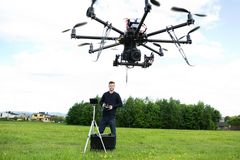 Male Technician Flying UAV Octocopter. With remote control in park Royalty Free Stock Images