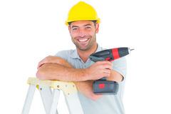 Male technician holding power drill on ladder. Portrait of male technician holding power drill on ladder over white background Royalty Free Stock Image