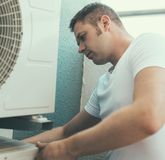 Air-conditioning system installation. Male technician installing air-conditioning system Royalty Free Stock Photos