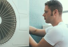Air-conditioning system installation. Male technician installing air-conditioning system Stock Photo