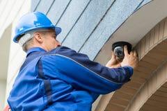 Male Technician Installing Camera. Close-up Of Mature Male Technician Installing Camera Stock Photography